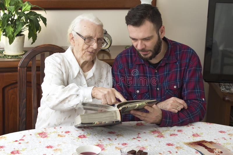 Old woman with her grandson sitting at the table in the living room and watching old photos. stock photo