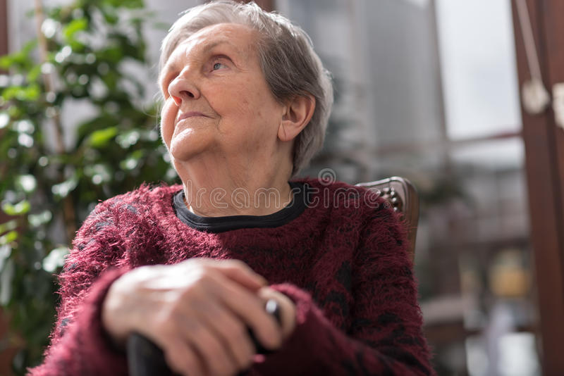Old woman with her hands on a cane. Old woman sitting with her hands on a cane royalty free stock photos