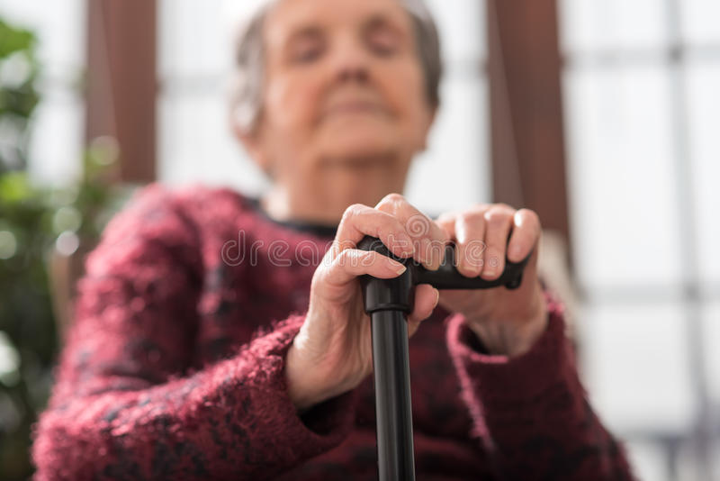 Old woman with her hands on a cane. Old woman sitting with her hands on a cane stock photos