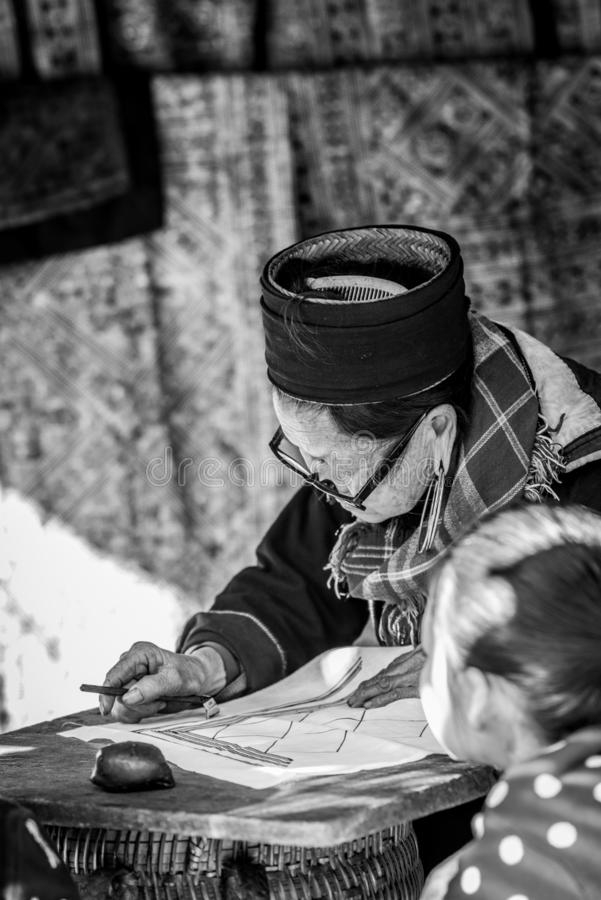 The old woman of Hmong tribe name is painting on to the white fabric. By the hot wax before being dyed at Catcat Village,Sapa,Vietnam stock photo