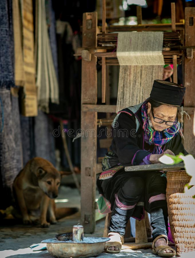 The old woman of Hmong tribe name is painting on to the white fabric. By the hot wax before being dyed at Catcat Village,Sapa,Vietnam stock photography
