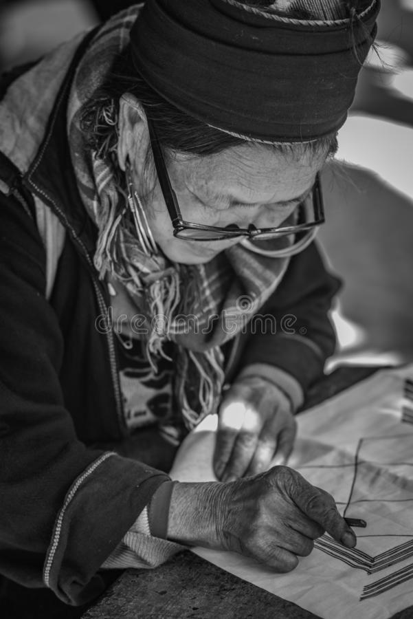 The old woman of Hmong tribe name is painting on to the white fabric. By the hot wax before being dyed at Catcat Village,Sapa,Vietnam royalty free stock image