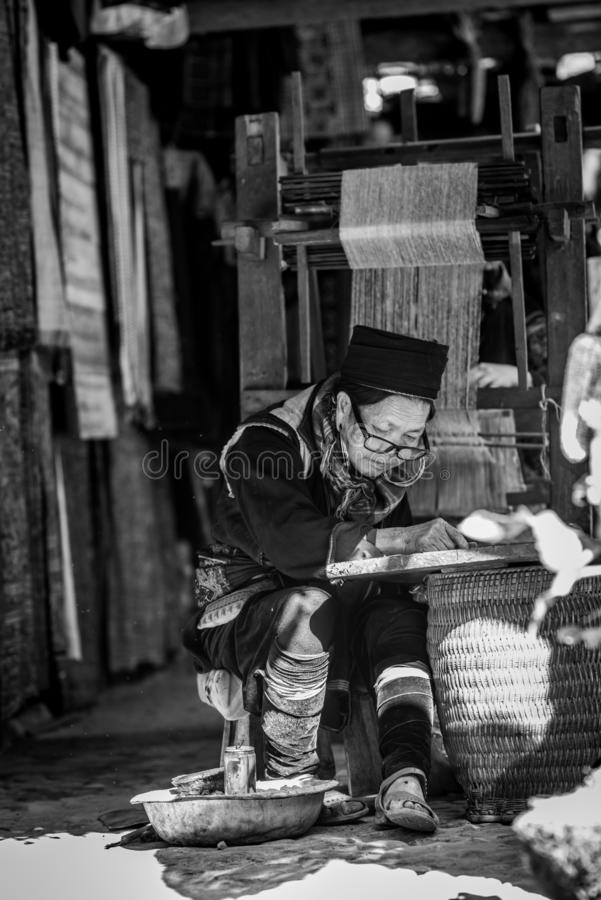 The old woman of Hmong tribe name is painting on to the white fabric. By the hot wax before being dyed at Catcat Village,Sapa,Vietnam royalty free stock photos