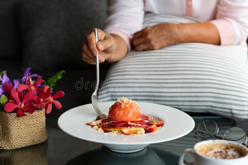 Old woman hold folk with freshly homemade Pancakes Strawberry Crumble on white dessert plate royalty free stock image