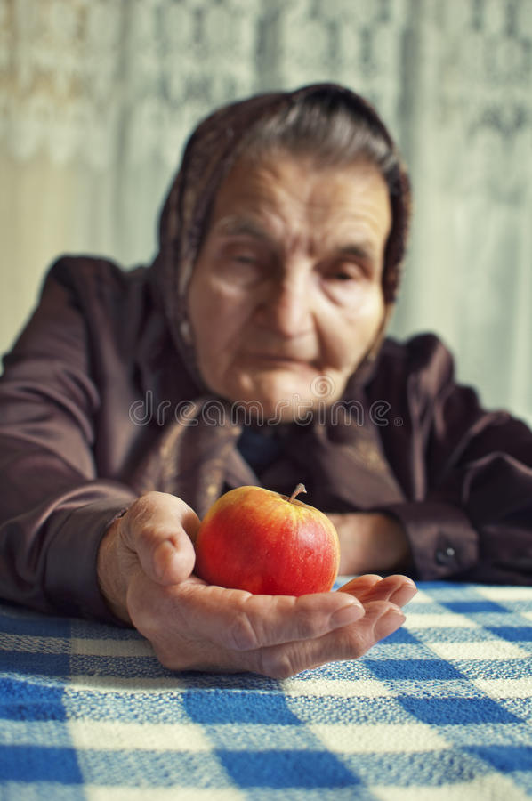 Old woman holding an apple. stock image