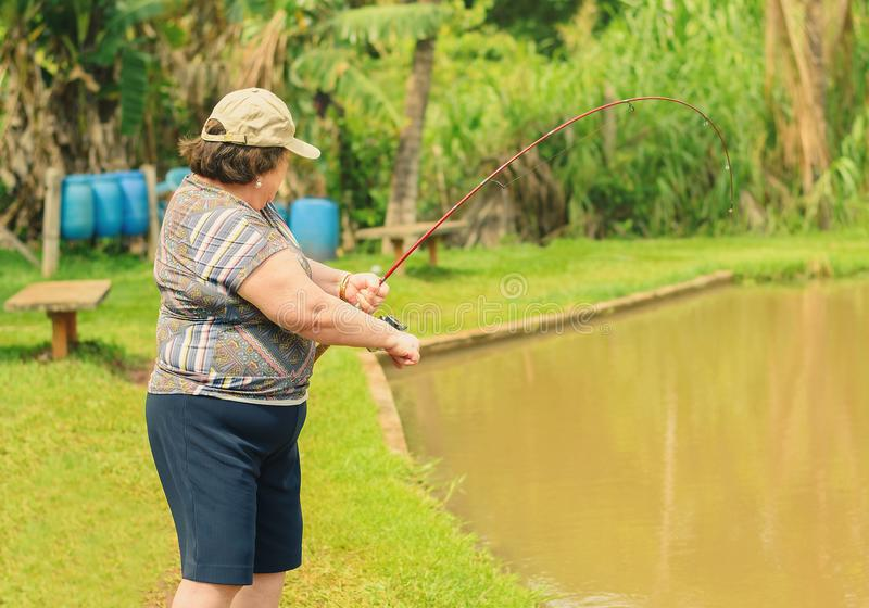 Old woman holding a fishing rod, hooking a fish on a lake. Brazilian woman descendant of japanese fishing stock image