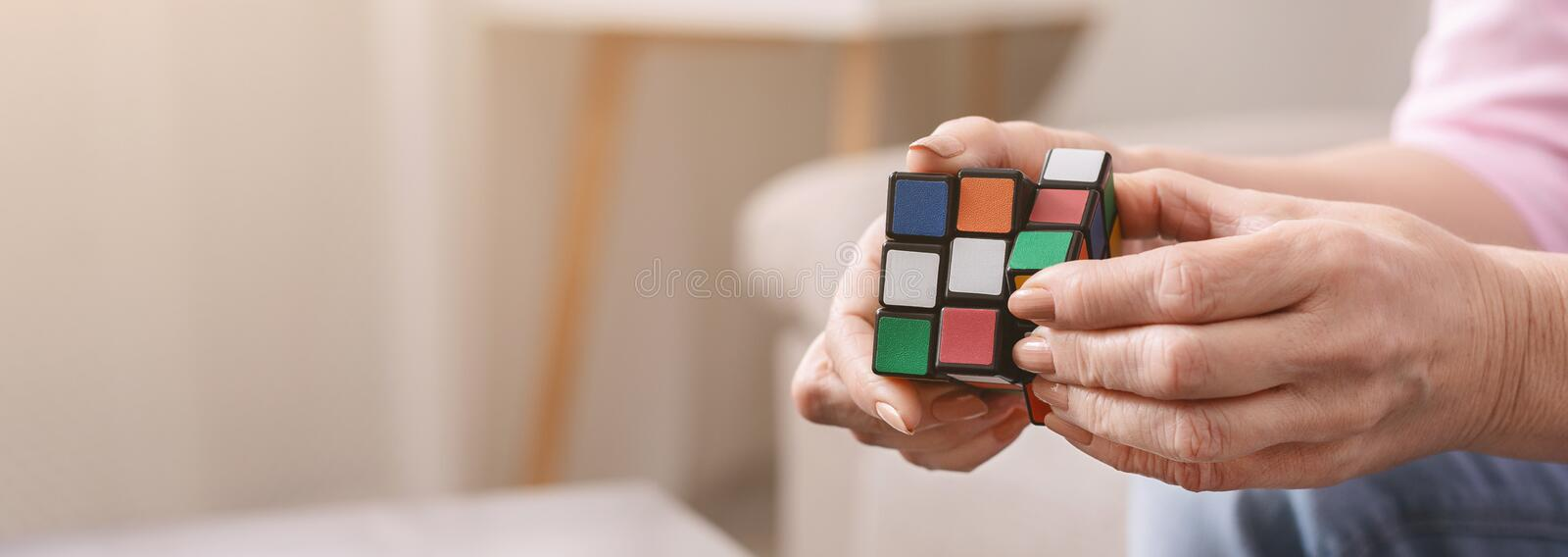 Old woman holding Rubik`s cube and playing with it stock image