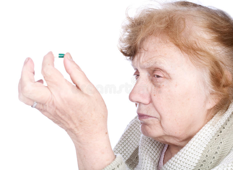 The old woman holds in hands capsule stock photography