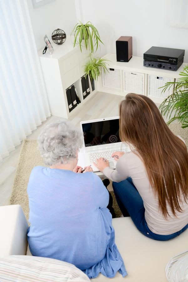 Old woman at home with cheerful young girl spending time together with laptop computer. Old women at home with cheerful young girl spending time together with a royalty free stock photography