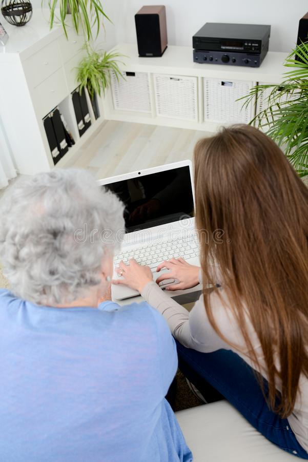 Old woman at home with cheerful young girl spending time together with laptop computer. Old women at home with a cheerful young girl spending time together with stock images