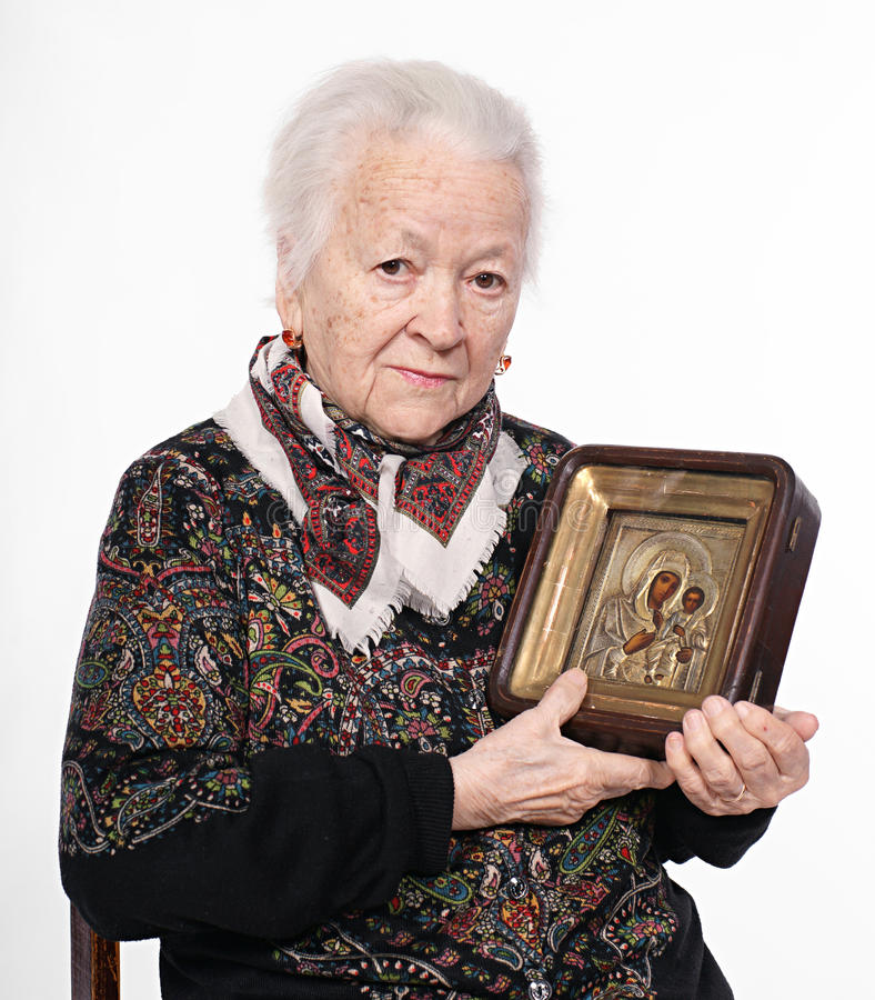 Old woman with icon. On a white background stock image