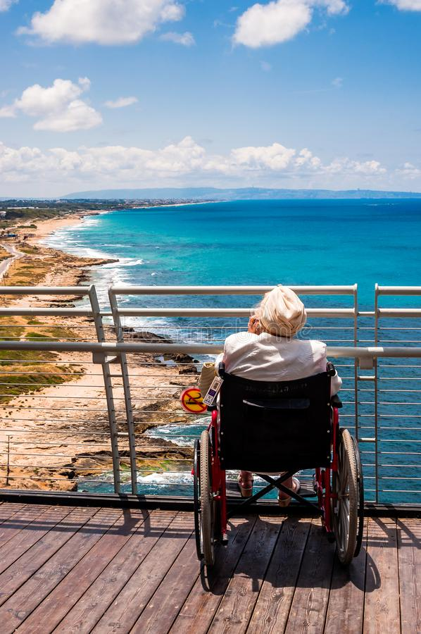Old woman invalid sitting on the wheelchair and talking mobile phone while looking to North Mediterranean Sea coast from Rosh. Rosh Hanikra, Israel - May 20 stock images
