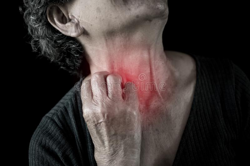 Old woman itching and painful in neck on black background. Dermatitis and Illness of the elderly medical concept royalty free stock photos