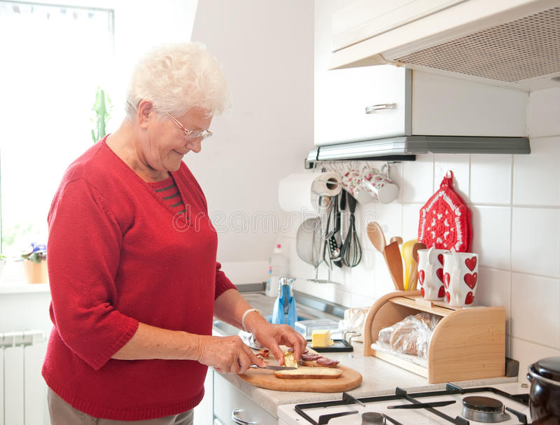 Download Old woman in the kitchen stock photo. Image of board - 22931184