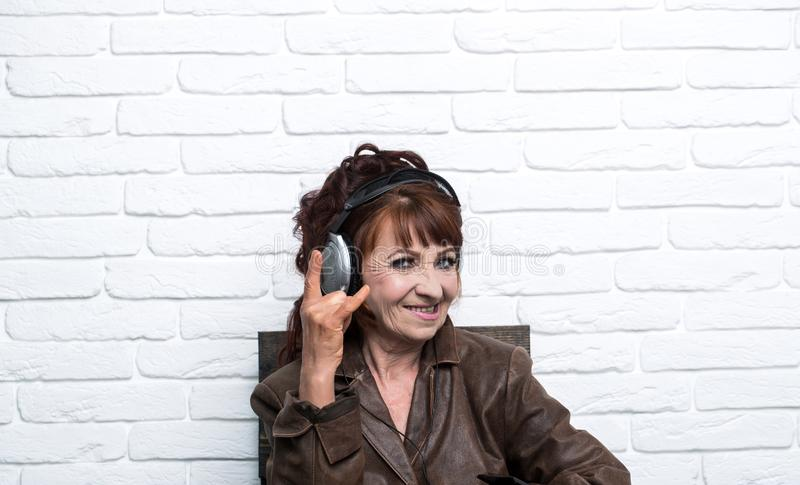 Old woman listen music in headphones on brick wall background stock photos