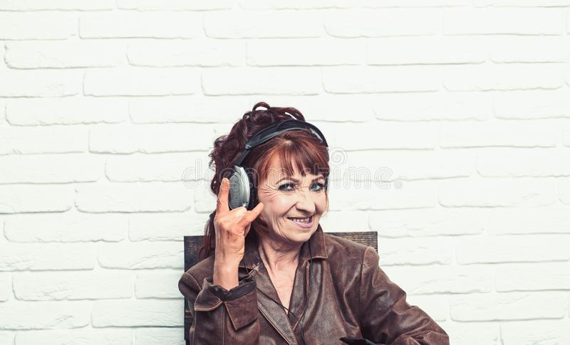 Old woman listen music in headphones on brick wall background stock image