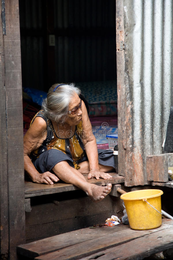 A old woman living in a slum stock image