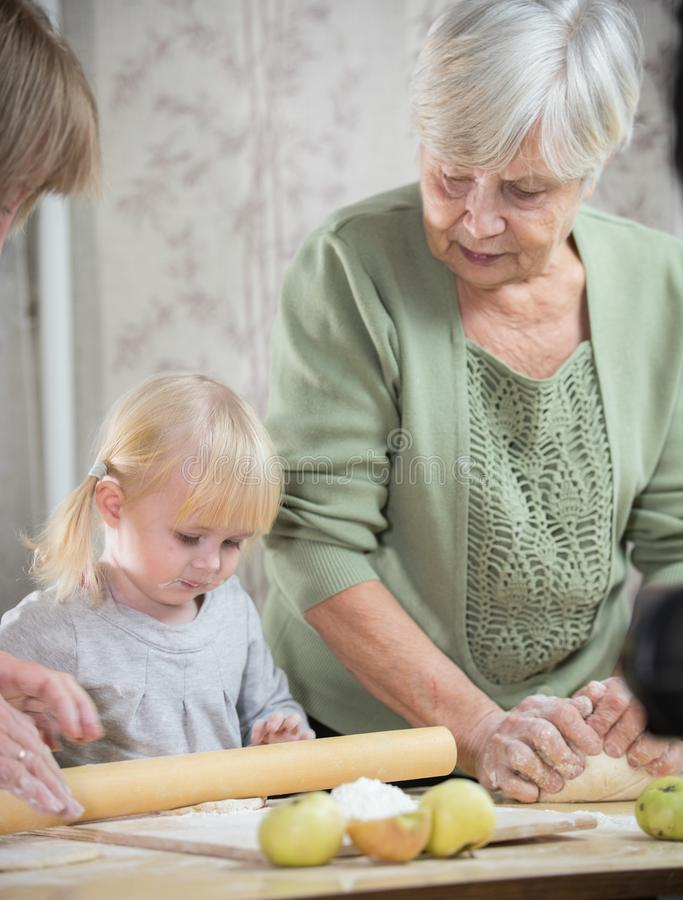 An old woman making little pies with her granddaughter. Rolling the dough. An old women making little pies with her granddaughter. Rolling the dough. Vertical royalty free stock images