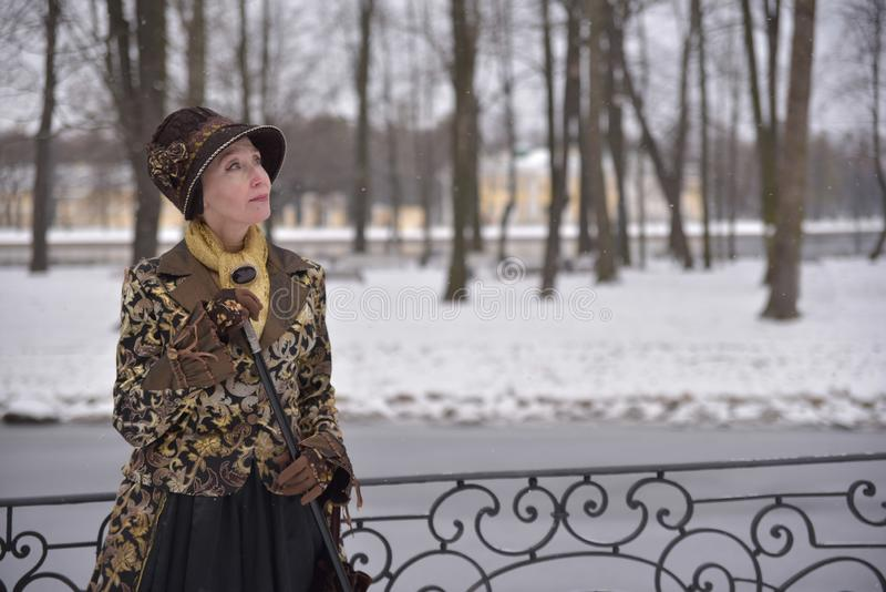 Old woman in old clothes. In the nature stock photography