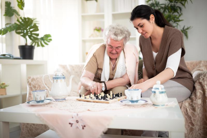 Old woman playing chess royalty free stock photo