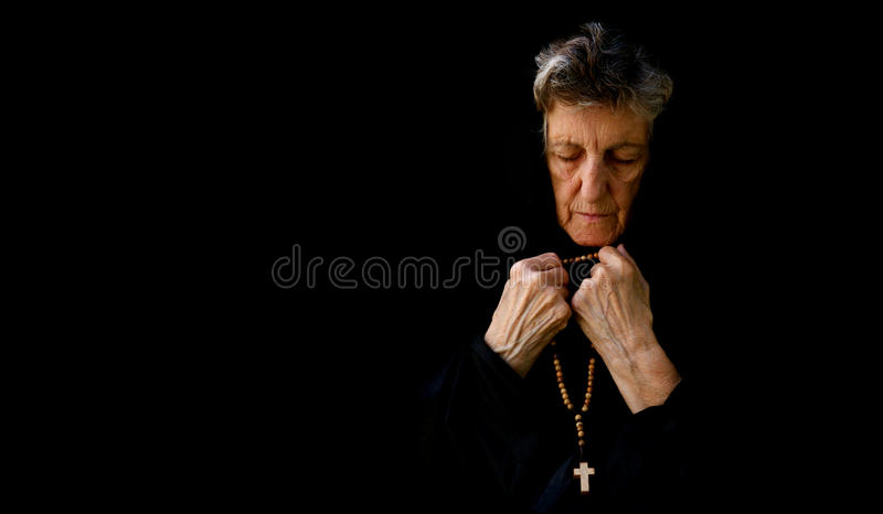 An old woman is praying in the garden. A senior woman between 70 and 80 years old, dressed in black is praying in the garden. Fron view royalty free stock image