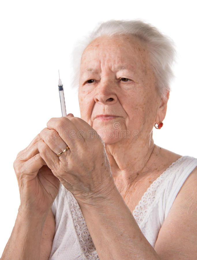 Old woman preparing syringe for making insulin injection stock photography