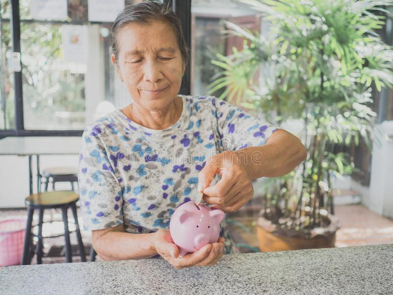 Old woman putting coin into Pink piggy bank. Saving money for future plan and retirement fund concept stock images