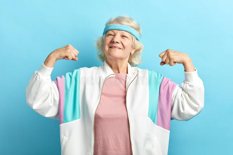 Old woman raising one hand, showing strength of her musculs, sport achievement. royalty free stock photos