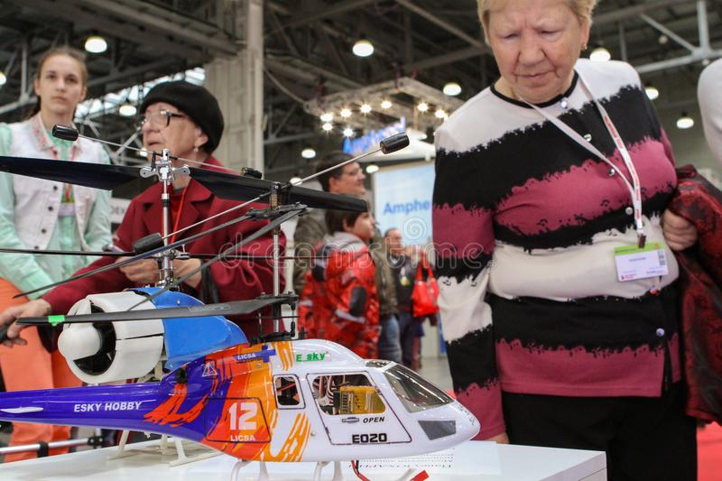 Old woman and RC helicopter, focus on the helicopter. Moscow - May 26, 2018: Old woman and RC helicopter, focus on the helicopter at the international exhibition royalty free stock photos