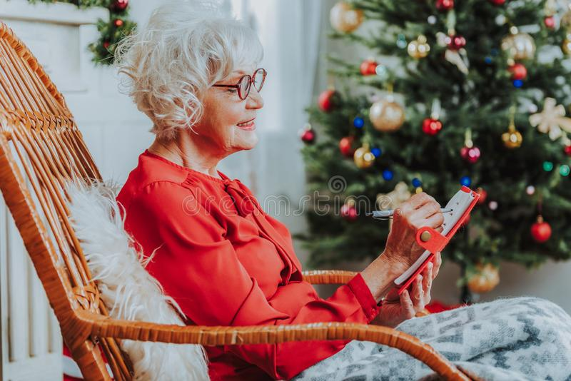 Old woman is relaxing in rocking chair stock image