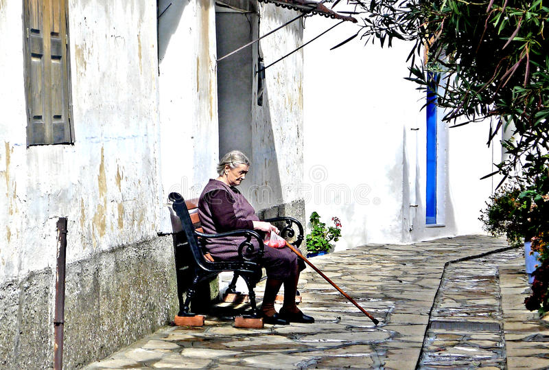 Old woman in Samos Greece. An old woman rests out of her home on the Greek island of Samos a aegean ancient and archaeological aristarchus as beautiful stock photos