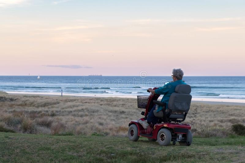 An old woman rides on a electric powered wheelchair parked on the beach at sunset time, in a lonely atmosphere. Lonely widow old stock photos