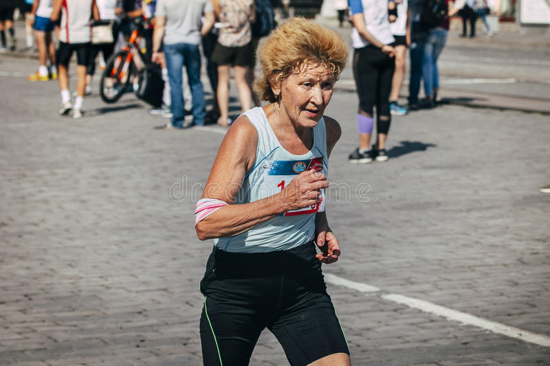 Old woman runner competes. Ekaterinburg, Russia - August 01, 2015: old woman runner competes during Marathon From Europe To Asia, Ekaterinburg, Russia - August stock photos