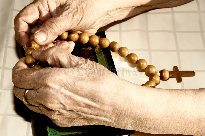 Old woman's hands holding rosary stock photo