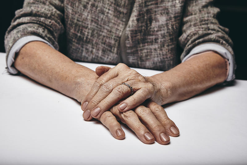Old Woman's Hands Resting On Grey Surface Stock Photo ...