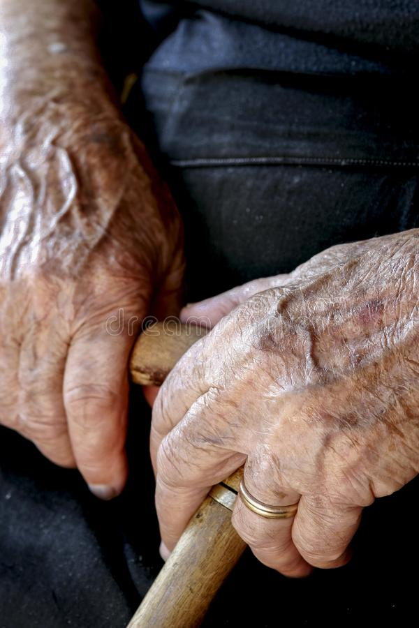 Old woman`s hands holding a cane royalty free stock photo