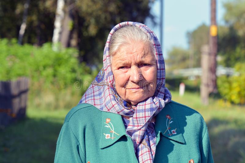 An old woman in a scarf. Portrait of a lonely old woman standing in a village royalty free stock photos