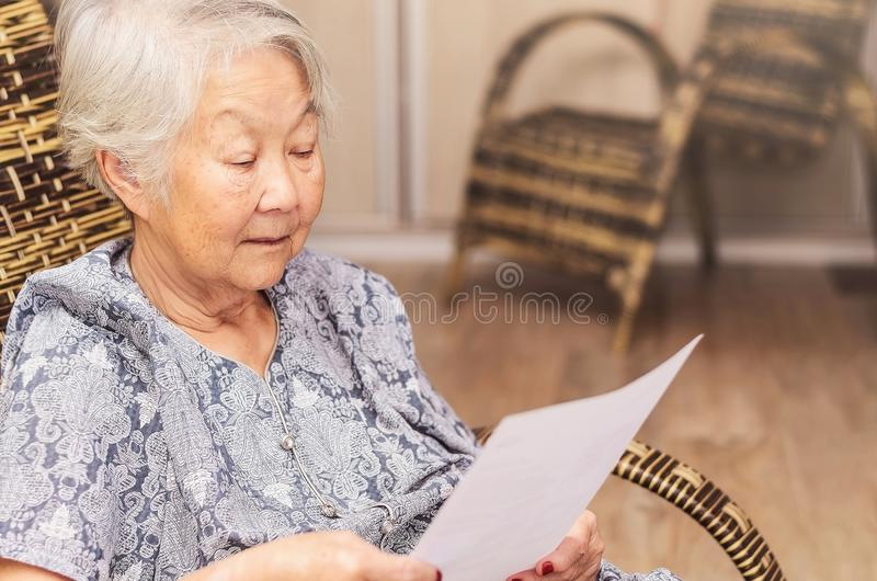 Old woman seated reading carefully a document or terms of a insurance. Old obaasan (grandma), japanese descendant. Old woman seated reading carefully a document royalty free stock photography