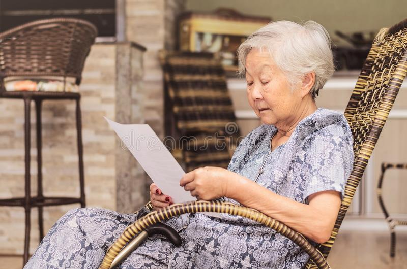 Old woman seated reading carefully a document or terms of a insurance. Old obaasan (grandma), japanese descendant. Old woman seated reading carefully a document royalty free stock image