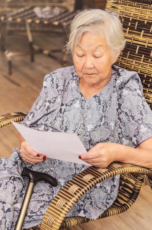 Old woman seated reading carefully a document or terms of a insurance. Old obaasan (grandma), japanese descendant. Old woman seated reading carefully a document stock photo