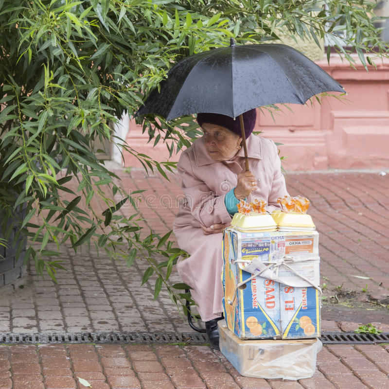 Old woman selling artware in the rain in nizhny novgorod ,russian federation. Old woman selling artware in the rain is taken in nizhny novgorod ,russian stock photo