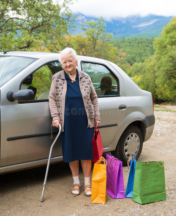 Old woman with shopping bags stock photography