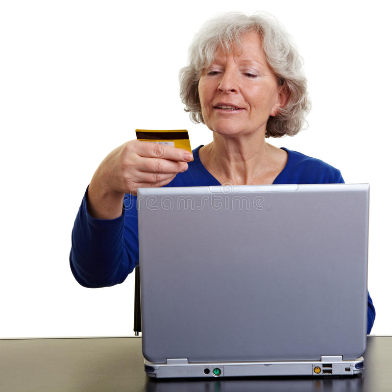 Old woman shopping online. Elderly woman shopping online with laptop and credit card stock photos