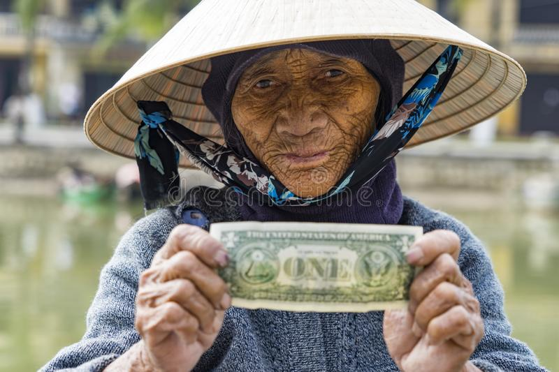 The tip. An old woman showing her tip from a customers at Hoi an, Vietnam royalty free stock photo