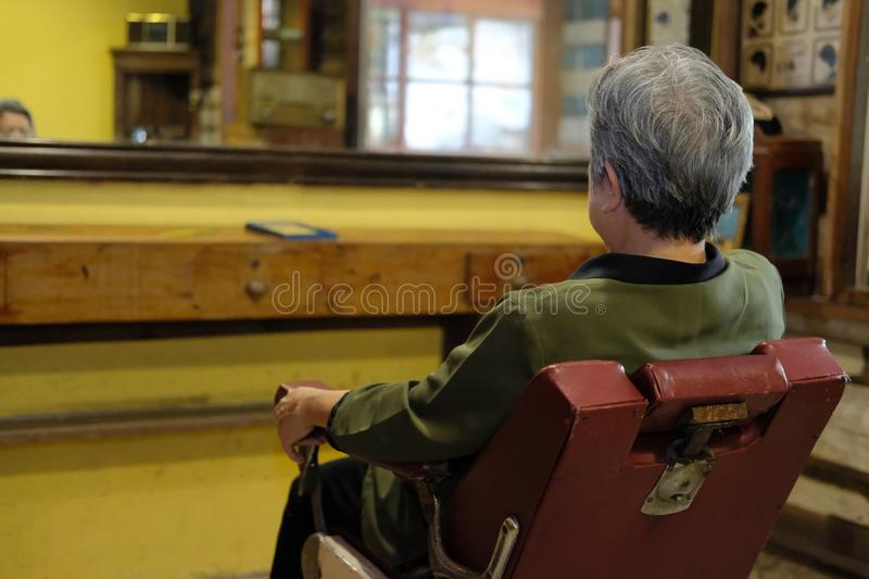 Old woman sit on stylish vintage barber chair in beauty salon shop stock image