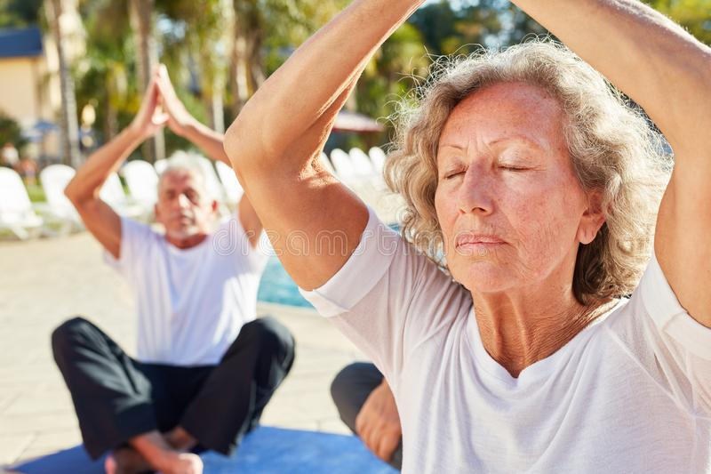 Old woman sits and meditates in the spa by the pool stock image