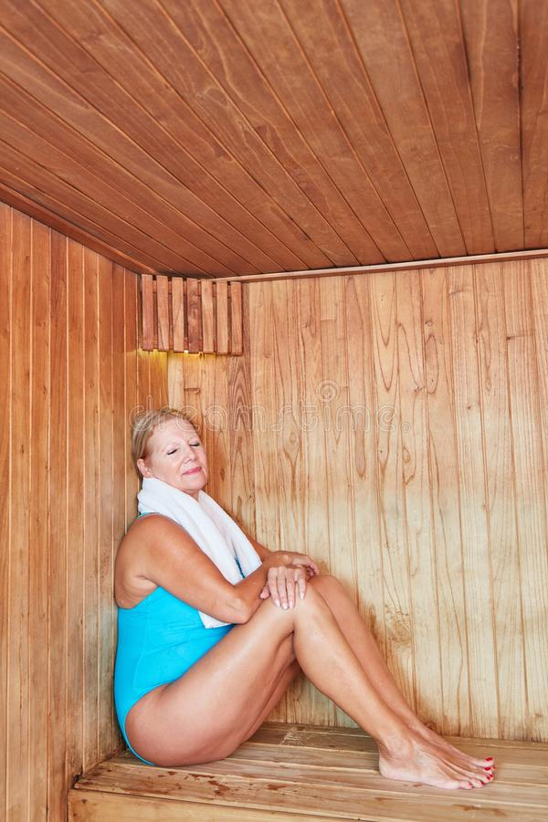 Old woman sits relaxed in the sauna stock photography