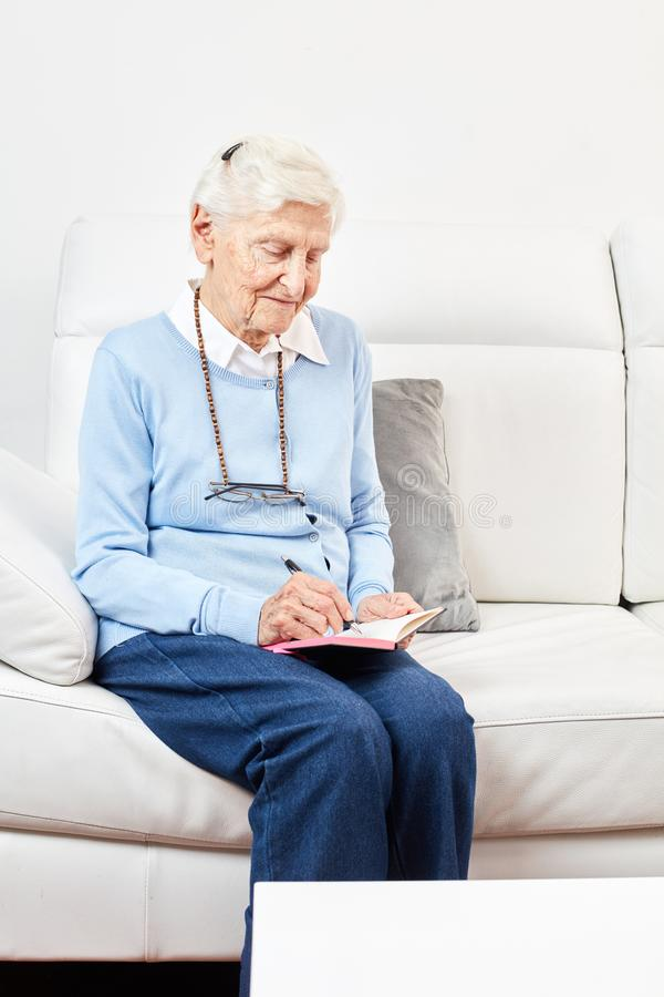 Old woman writes in a notebook stock photos