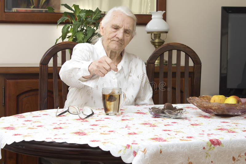 The old woman sits at a table in the living room and make tea in a glass. stock photo