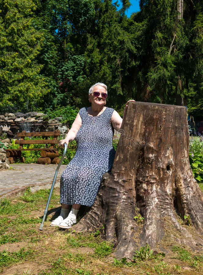 Old Woman Sitting On A Bench Stock Photo
